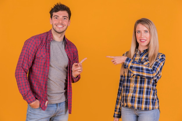 Portrait of a young couple pointing their fingers to each other against an orange backdrop Free Photo