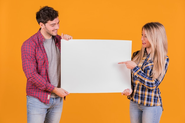 Portrait of a young couple pointing their fingers on the white placard against an orange backdrop Free Photo