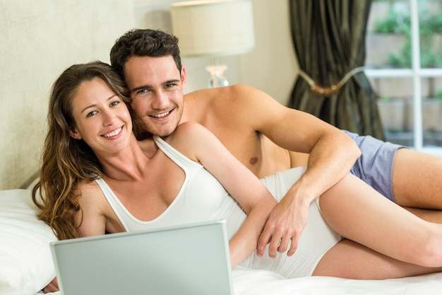 Portrait of young couple relaxing on bed in bedroom Premium Photo