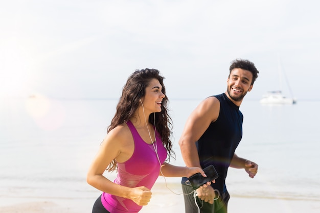 Portrait of young couple running on beach, happy male and female runner jogging together Premium Photo