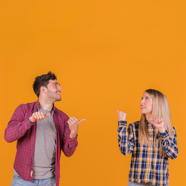 Portrait of a young couple showing thumb up to back against an orange background Free Photo