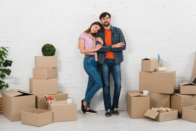 Portrait of young couple standing against white wall with new cardboard boxes in new house Free Photo