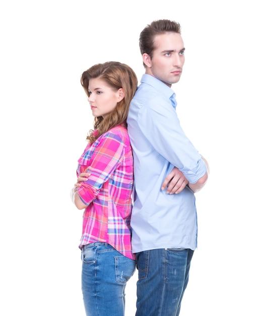 Ritratto di giovane coppia in piedi schiena contro schiena e pensiero isolato sul muro bianco. Foto Gratuite