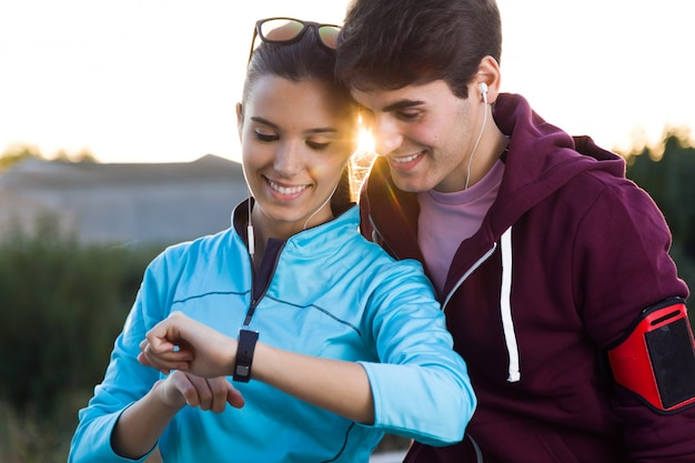 Portrait of young couple using they smartwatch after running. Free Photo