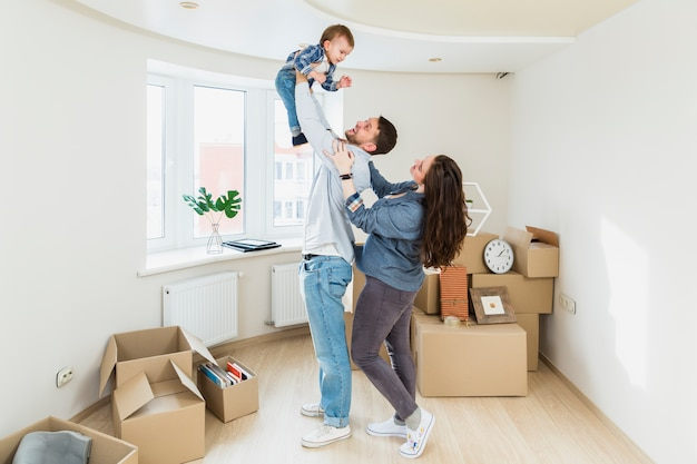 A portrait of young couple with a baby and moving cardboard boxes in a new home Free Photo