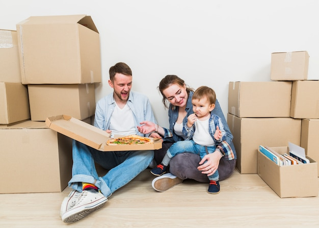 Portrait of young couple with their son enjoying the pizza treat in their new house Free Photo