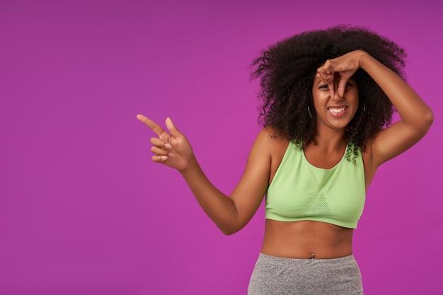 Ritratto di giovane donna dalla pelle scura riccia con acconciatura casual in piedi sul viola e chiusura del naso con la mano, evitando il cattivo odore e mostrando da parte con il dito indice Foto Gratuite