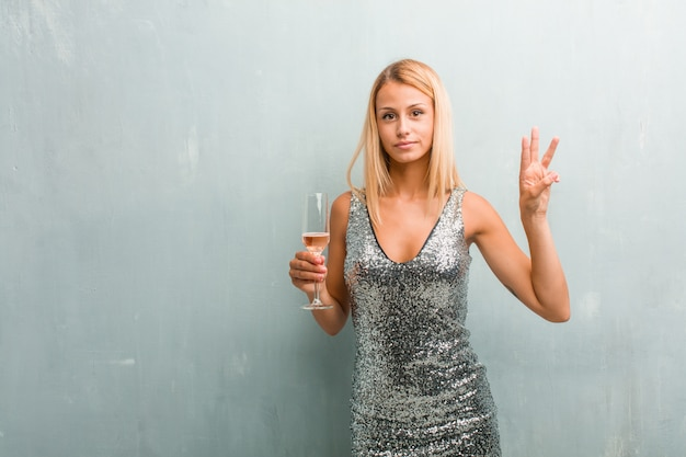 Portrait of young elegant blonde woman showing number three, symbol of counting Premium Photo