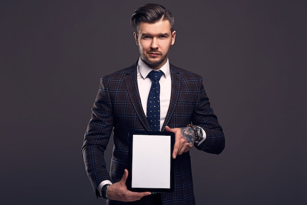 Portrait of a young elegant brutal man with tablet Premium Photo