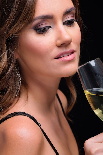 Portrait of young elegant woman drinking champagne against black Premium Photo
