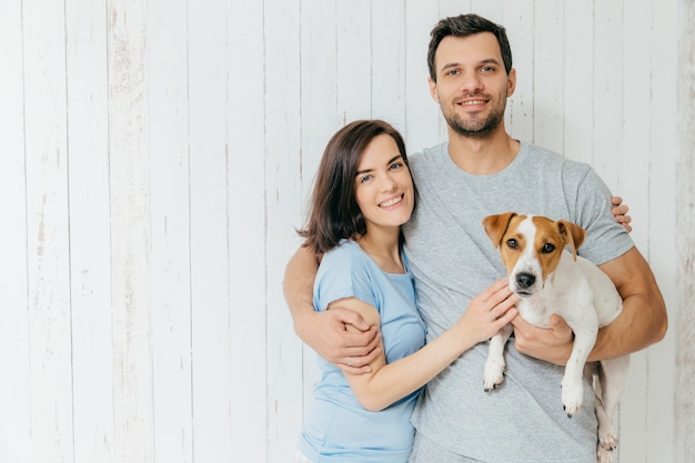 Portrait of young family couple embrace each other and hold their favourite pet Premium Photo