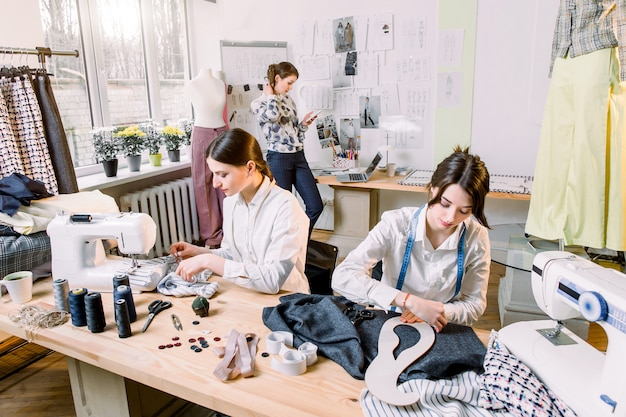 Portrait Of Young Fashion Dressmakers Women At Work Dressmaker Tailor Fashion And Showroom Concept Portrait Of Talented Female Dressmakers Working With Textile For Sewing Clothes Premium Photo