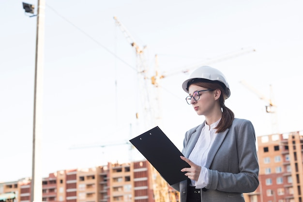 Portrait of young female architect working on clipboard at architectural project Premium Photo