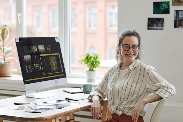 Portrait of young female photographer smiling at camera while posing at desk with photo editing software on computer screen, copy space Premium Photo