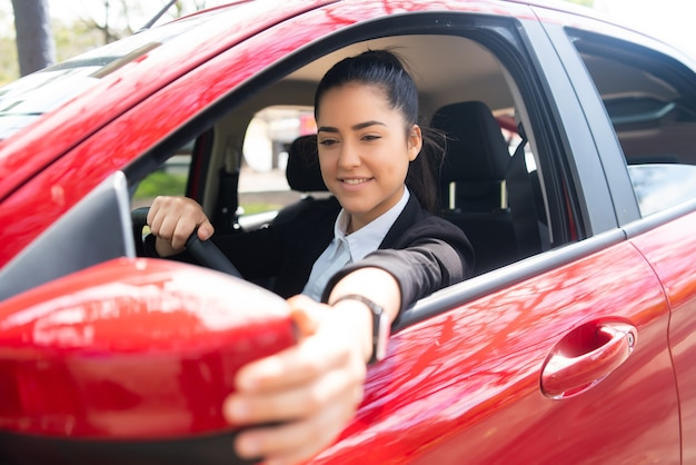 Portrait of young female professional driver in a car and moving rear view wing mirror. Premium Photo