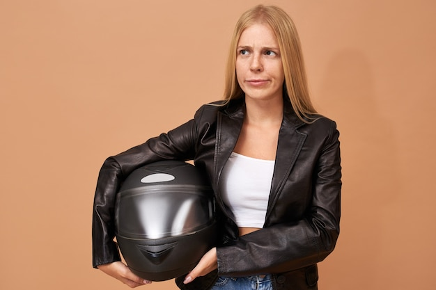 Portrait of young female rider with teeth braces and long straight hair posing isolated in black leather jacket Free Photo