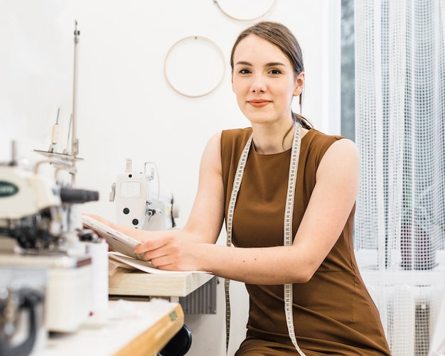 Portrait of a young female seamstress looking at camera Free Photo