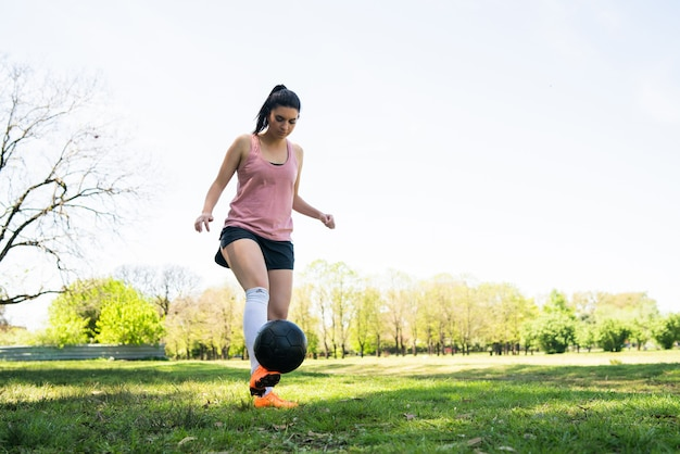 Portrait of young female soccer player running around cones while practicing with ball on field Free Photo