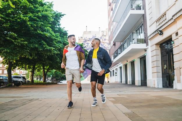Ritratto di giovane coppia gay tenendo le mani e correndo insieme alla bandiera arcobaleno in strada. lgbt e concetto di amore. Foto Gratuite