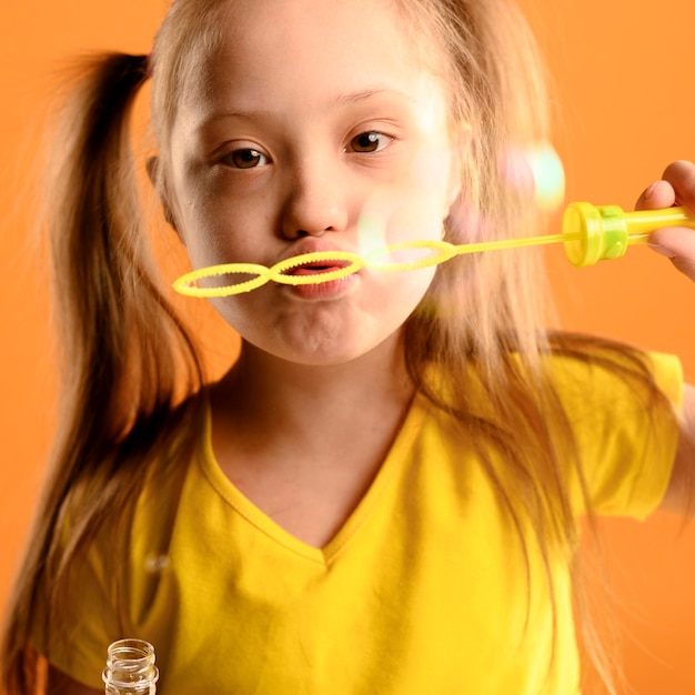 Portrait of young girl blowing bubbles Free Photo