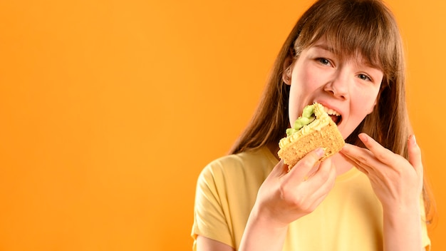 Portrait of young girl eating cake with copy space Premium Photo