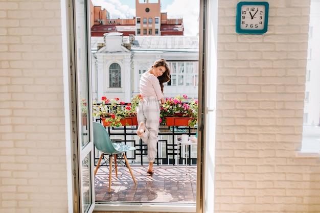 晴れた朝に市のバルコニーに移動するパジャマの肖像少女。彼女の長い髪は風になびいていて、笑っています。 無料写真