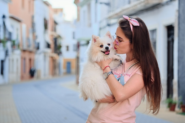 Portrait of a young girl kissing her white fluffy pomeranian dog. Premium Photo