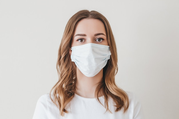 Portrait of a young girl in a medical mask isolated on a white wall wall. young woman patient Premium Photo