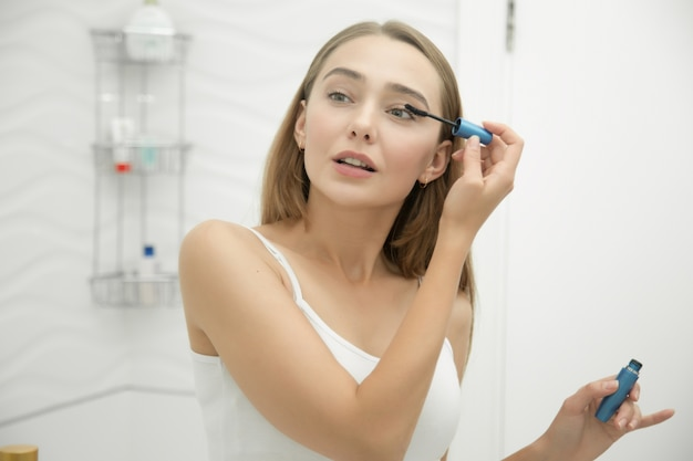 Portrait of a young girl putting on mascara Free Photo