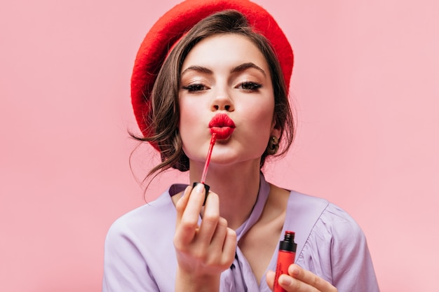 Portrait of young girl in red beret painting her lips with bright lipstick on pink background. Free Photo