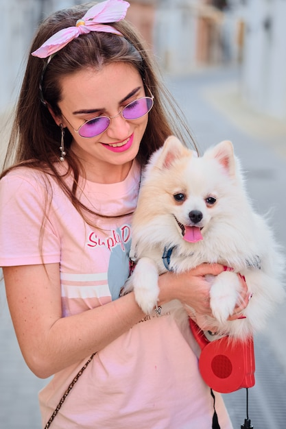 Portrait of a young girl walking with a white fluffy pomeranian. Premium Photo