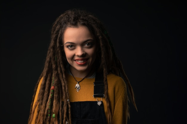 Portrait of a young girl with dreads on black Premium Photo