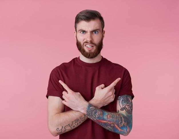 Ritratto di giovane uomo barbuto rosso accigliato bello malinteso in maglietta rossa, si leva in piedi su sfondo rosa guarda la telecamera con disgusto e punti in direzioni diverse. Foto Gratuite