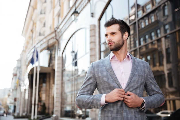 Portrait of a young handsome man buttoning his jacket Free Photo