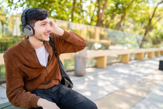 Ritratto di giovane uomo bello che ascolta la musica con le cuffie mentre è seduto all'aperto. concetto urbano. Foto Gratuite