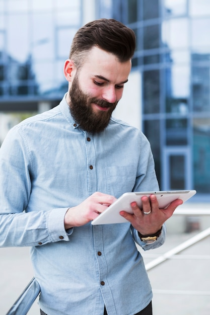Portrait of a young handsome man using digital tablet Free Photo