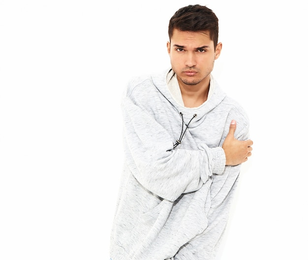 Portrait of young handsome model man dressed in gray casual hoodie clothes posing on white wall. isolated Free Photo