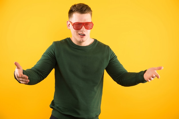 Portrait of young handsome smiling guy with sunglasses showing gesture with open arms Premium Photo