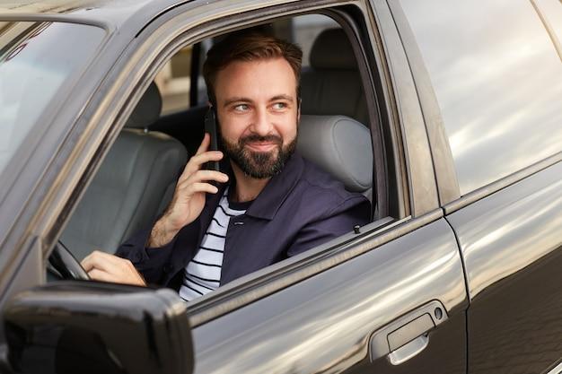 Ritratto di giovane uomo barbuto di successo bello con una giacca blu e una maglietta a righe, si siede al volante della macchina e attende una risposta al telefono dalla sua ragazza. Foto Gratuite