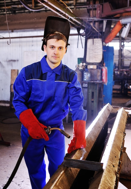 Portrait of a young handsome welder with a welding machine in his hands Premium Photo