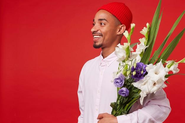 Ritratto di giovane ragazzo attraente afroamericano felice, indossa in camicia bianca e cappello rosso, distoglie lo sguardo e tiene il mazzo, si leva in piedi su sfondo rosso e sorridente. Foto Gratuite