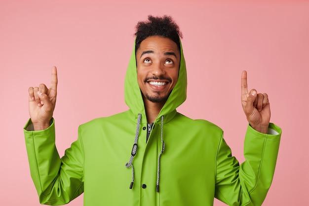Ritratto di giovane ragazzo bello afroamericano felice si alza, sorride ampiamente, vuole attirare la vostra attenzione per copiare lo spazio, puntare le dita e guardarlo. Foto Gratuite