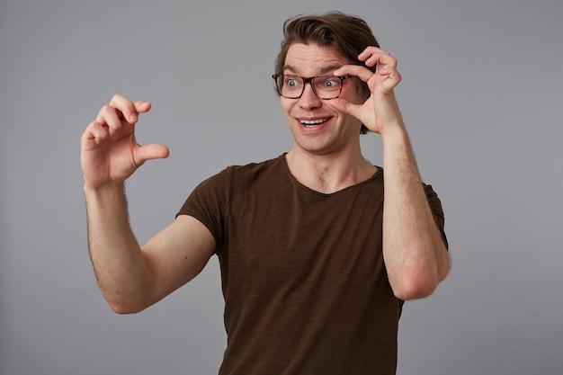 Ritratto di giovane uomo stupito felice con gli occhiali, si erge su sfondo grigio guarda attraverso gli occhiali, mostra le dita qualcosa di minuscolo. Foto Gratuite
