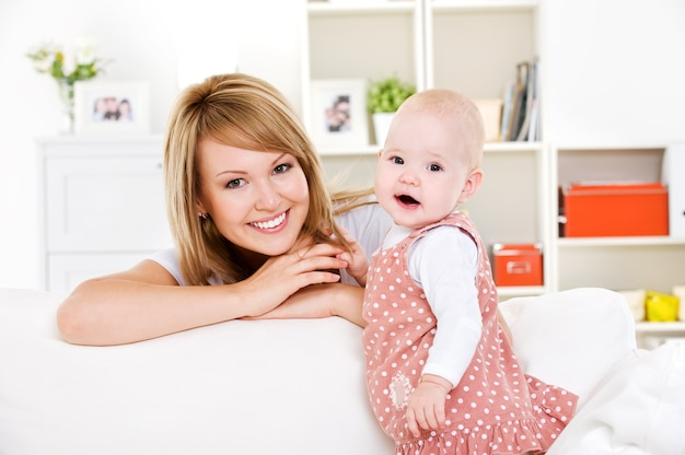 Ritratto di giovane madre felice con neonato a casa Foto Gratuite