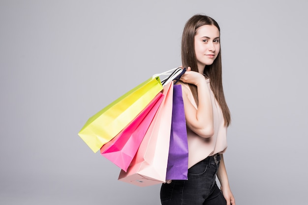 Portrait of young happy smiling woman with shopping bags over white wall Free Photo