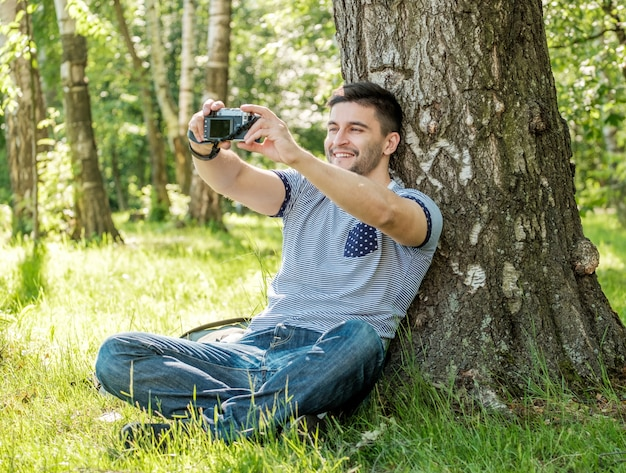 Portrait of young hipster man with camera outdoors. young male photographer making selfie on summer day. Premium Photo