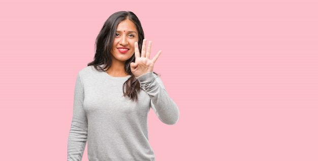 Portrait of young indian woman showing the number four, symbol of counting Premium Photo