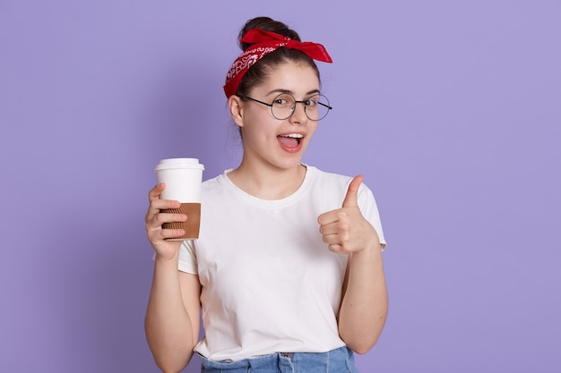 Portrait of young lady in casual white t shirt standing with cup of coffee to go isolated over lilac space. pretty girl happily showing thumb up gesture while  and winks. Free Photo