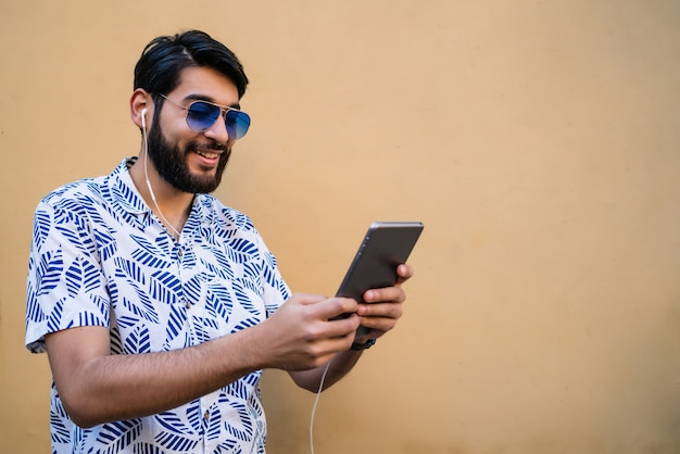 Portrait of young latin man using his digital tablet with earphones against yellow wall. technology and urban concept. Free Photo