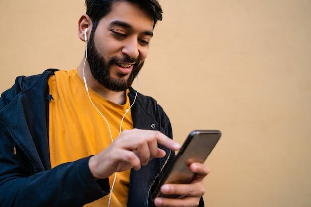 Ritratto di giovane uomo latino utilizzando il suo telefono cellulare con auricolari contro il giallo Foto Gratuite